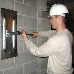 installing a wall anchor to repair an bowing foundation wall in Brookhaven